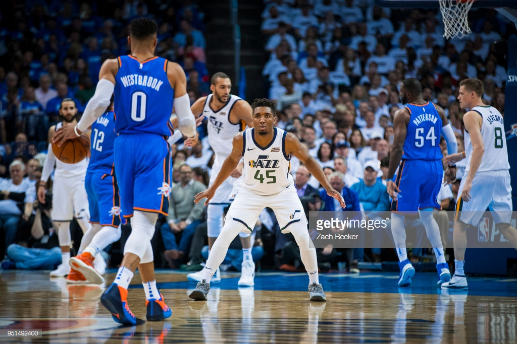 OKLAHOMA CITY, OK - APRIL 25: Donovan Mitchell #45 of the Utah Jazz guards Russell Westbrook #0 of the Oklahoma City Thunder in Game Five during Round One of the 2018 NBA Playoffs on April 25, 2018 at Chesapeake Energy Arena in Oklahoma City, Oklahoma. NOTE TO USER: User expressly acknowledges and agrees that, by downloading and or using this photograph, User is consenting to the terms and conditions of the Getty Images License Agreement. Mandatory Copyright Notice: Copyright 2018 NBAE (Photo by Zach Beeker/NBAE via Getty Images)